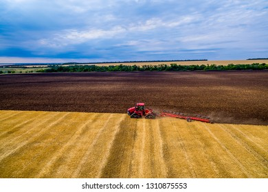 red tractor cultivates the land for planting crops. Aerial view Farmer in tractor preparing land with seedbed cultivator as part of pre seeding activities in early spring season of agricultural works