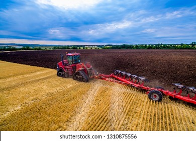red tractor cultivates the land for planting crops. Aerial view of cultivated land tractor