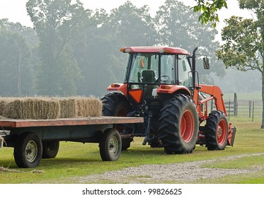 Red tractor hauling bales of hay