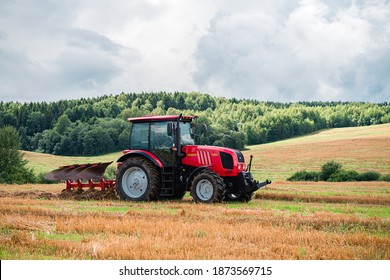 Red Tractor Plowing in Autumn, Farmer plowing stubble field in tractor preparing plows the land, agricultural works at farmlands, agriculture tractor-landscape