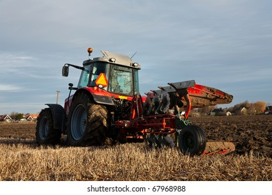 Red Tractor Plowing the field
