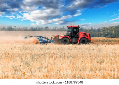 Red tractor plowing field, raising clouds of dust
