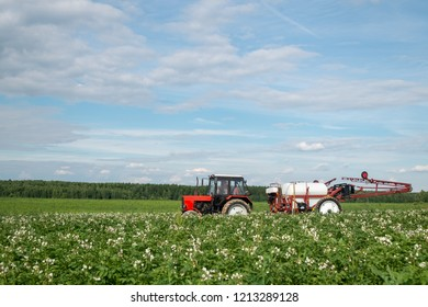 red tractor sprayer in the field doing chemical treatment to the plants