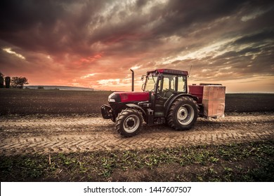 Red tractor used for bricks transportation during colorful and vibrant sunset in the field.