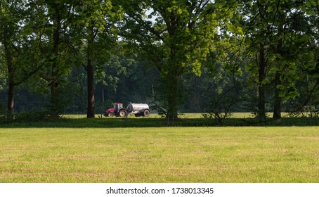Red tractor with water tank on field