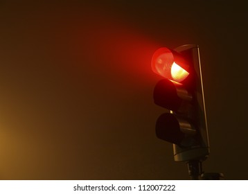 Red traffic light in fog