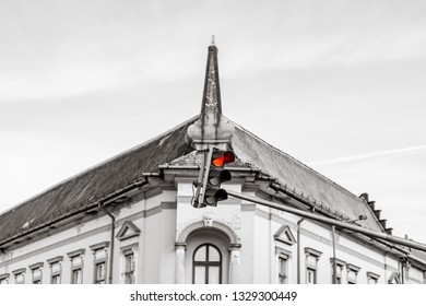 Red traffic light in front of old building in an old town: concept of urbanization and traffic ruining old town cityscapes. Color splash effect on the red traffic light