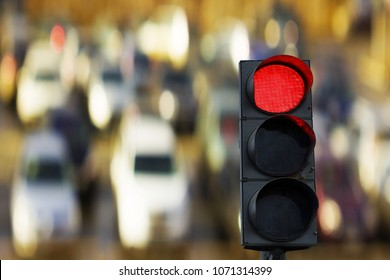 Red traffic light on the background cars.