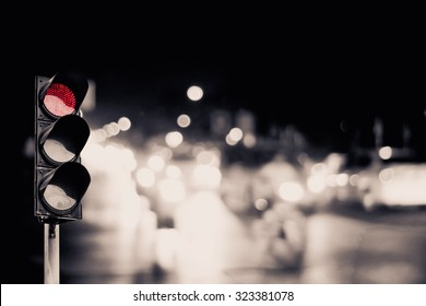 Red traffic light on the road in night city. dangerous signal stop crash driving highway,expressway; Blurred background of car dark fast truck surveillance security with semaphore. safety street