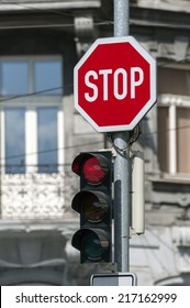 Red traffic light on and stop sign.