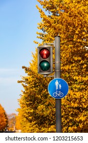 Red Traffic Light for Pedestrians in Finland. In the background there are yellow trees and a blue sky. It's autumn.