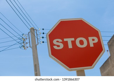red traffic stop sign and power lines on a pole