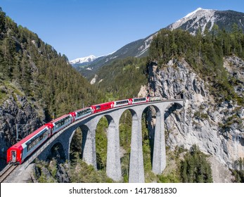 Red train of Bernina Express on the Landwasser viaduct. Unesco World Heritage in the Swiss Alps. Filisur - Albula