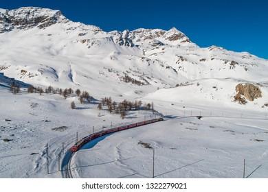 Red train of Bernina in winter season, aerial view. Bernina Express - UNESCO