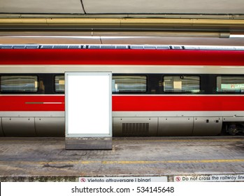red train carriage behind a blank billboard, with empty platform - Shutterstock ID 534145648