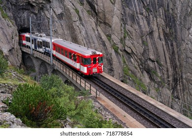 Red train entering the tunnel at Devil's bridge at St.Gotthard, Switzerland