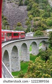 Red train on Brusio viaduct, Switzerland.