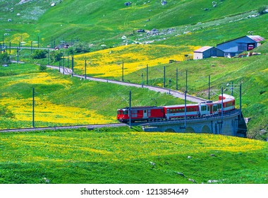 Red train passing through stone bridge in green valley at Andermatt