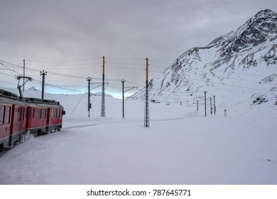 Red train running in the snow in swiss alps in winter