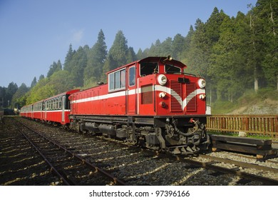 Red train under blue sky on railway forest in Alishan National Scenic Area, Taiwan, Asia.