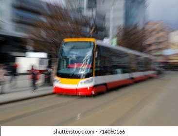 red tram on the street under blurred motion