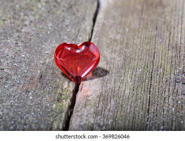 Red transparent glass heart on old gray boards. Close up