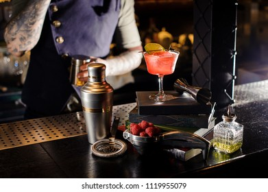 Red transperent cocktail in the ornate glass decorated with lime standing on the books on the bar counter