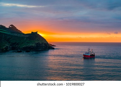 A red trawler boat returns back to Fowey at dawn a couple of hours before it snows for the first time in 8 years