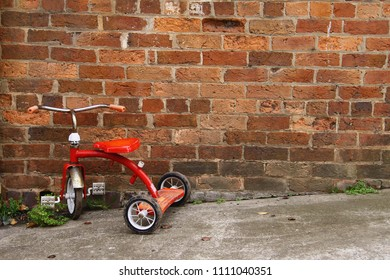 Red tricycle against a brick wall