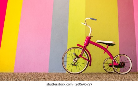 Red Tricycle In Front Of Colorful Wall