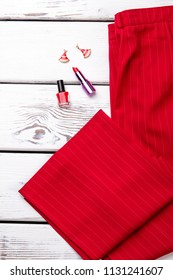 Red trousers with accessories. Folded pants, lipstic, lacquer and earrings.