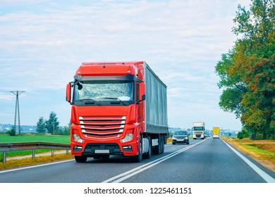 Red Truck in the alphalt road in Poland. Lorry transport delivering some freight cargo.