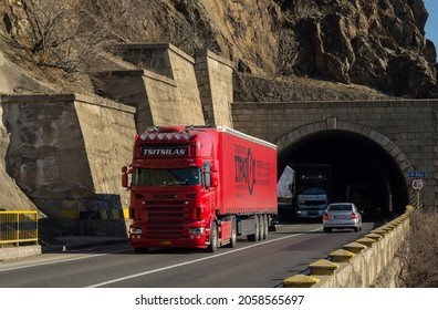 Red truck carrying commercial freight on the mountain highway, at the exit of a tunnel. This is a Scania truck. Cargo transportation concept. Cars in traffic. Severin, Romania, October 15, 2021