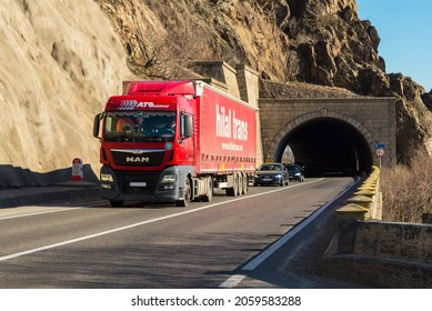 """Red truck carrying freight on the highway, at the exit of a tunnel, from below the mountain ridges. This is a MAN truck and belongs to the Turkish company """"Hilal Trans"""". Severin, October 17, 2021"""