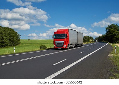 Red truck driving on asphalt road in a rural landscape. White truck coming from afar. Sunny summer day with blue skies and white clouds.