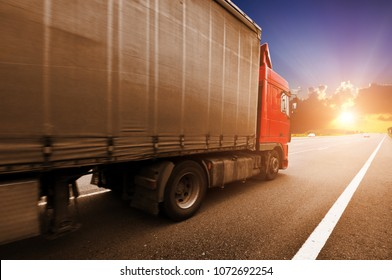 Red truck with the grey trailer on the countryside road against a night sky with a beutiful sunset