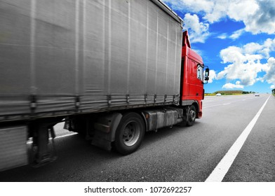 Red truck with the grey trailer on the countryside road against blue sky with clouds