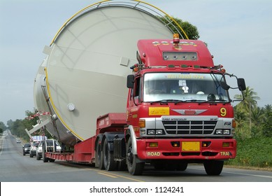 Red truck hauling a large tank
