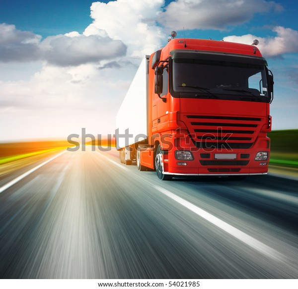 Red truck on blurry asphalt road over blue cloudy sky background