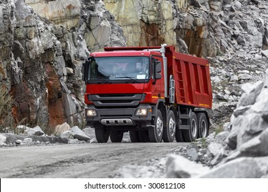 Red truck transports the rock in the quarry.