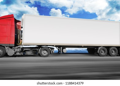 Red truck and a white trailer with space for text driving fast on the winter countryside road with snow against blue sky with clouds