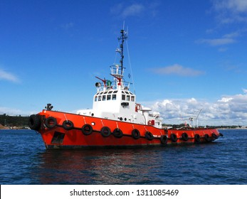 Red Tug at anchor in estuary bay awaiting next towing operation.