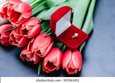 red tulip bouquet and diamond engagement ring