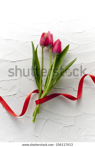 red tulip bouquet on white wall