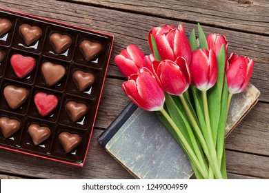 Red tulip flowers bouquet and gift box with heart chocolate. Valentine's day greeting card