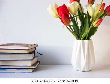 red tulips and books  on white background. Spring flowers.