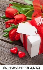 Red tulips, candy hearts and gift box over wooden table