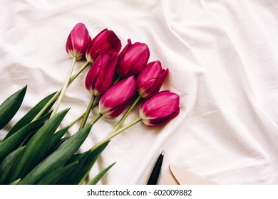 Red tulips with an envelope and a pen on the sheet with folds. Spring flowers in bed.