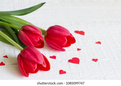 Red tulips and hearts on wooden white background celebration mothers day concept