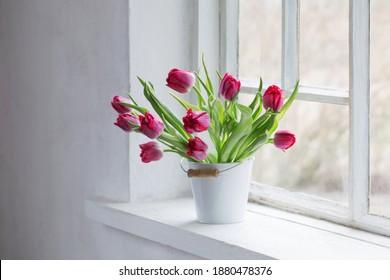 red tulips on old white windowsill - Shutterstock ID 1880478376